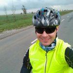 Autor na szosie. Na głowie ma kask rowerowy, okulary oraz żółtą kamizelkę rowerową.