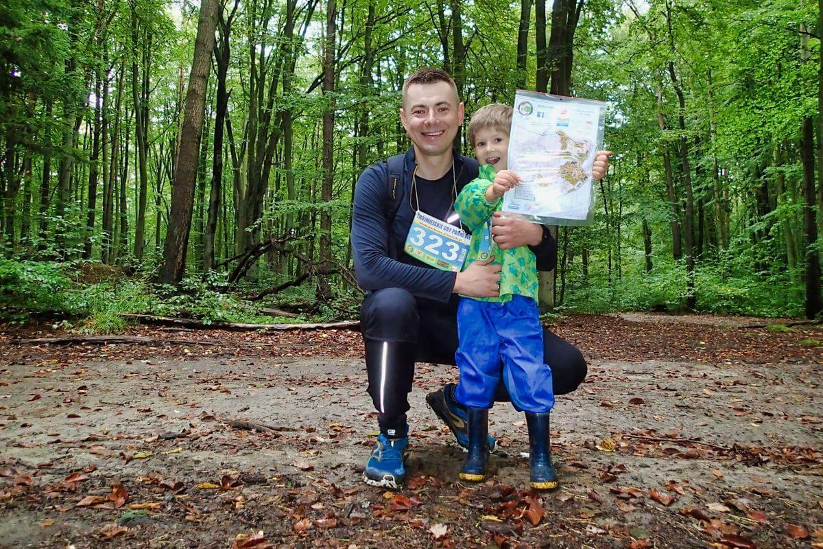 Autor z synem na trasie marszu. Chłopiec trzyma w ręku mapę. W tle leśne drzewa.