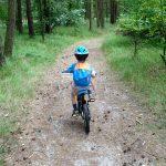 Olek jedzie na rowerze po leśnej ścieżce.